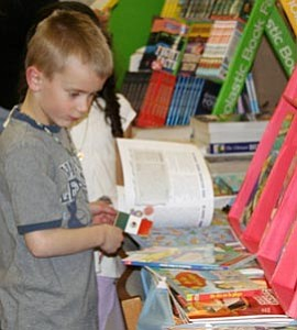 Dylan Nash browses at the Scholastic Book Fair at Grand Canyon School Library. The fair will be open today and tomorrow at lunch and from 3-4:30 p.m.