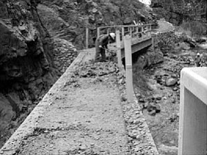 A trail crew works to clear and stabilize the bridge on the North Kaibab Trail.