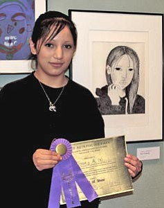 Ninth-grader Josey Araiza, with her self-portrait, which was named Best of Show at the opening of the Arts for Our Park student exhibit at Kolb Studio. More than 100 student works are on display through March in recognition of Student Art Month.