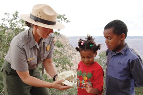 Photo courtesy National Park Service Ranger Jessica Collins shares a mountain lion skull with Jakiah and Dante Smith Evans.