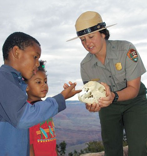 Submitted photo Ranger Jessica Collins shares a mountain lion skull with Dante and Jakiah Smith Evans.