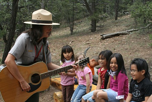 Ranger SuZan Pearce leads students in a sing-along about national parks.