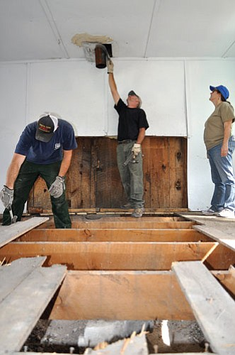 <br>Submitted photo<br> North Kaibab Civil Engineering Technician Ed Kolle inspects the stove pipe at Jump Up Cabin Sept. 9 as workers pry away old floorboards. The historic cabin is undergoing restoration work that is funded by federal stimulus money.