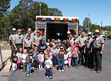 Photo/Bill Wright<br> Members of the Visitor and Resource Protection division of the Grand Canyon Park Service Rangers along with Kaibab Learning Center Director Jeanne Yost, KLC employees and students stand in front of an ambulance used to deliver donated supplies to the Montessori school and daycare facility.