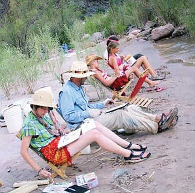NPS photo<br> Youth participants and one of their river guides hone their artistic skills on the shore of the Colorado River in Grand Canyon National Park.