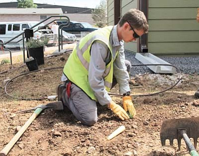 Courtesy photo<br> Student Conservation Intern Joe Broberg plants native grass at the Paiute Apartments.
