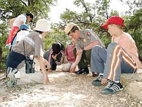 Submitted photo<br> A group of children examine fossils with the help of a ranger during a previous National Fossil Day event at Grand Canyon National Park.