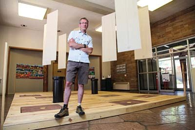 "Installation artist Shawn Skabelund stands on his recently completed work, located in the Grand Canyon National Park Headquarters. The work, entitled ""The Price of Entrance"" will be on display through Sept. 15. Ryan Williams/WGCN<br /><br /><!-- 1upcrlf2 -->"