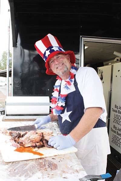 John Crim serves up tasty barbecue during last year's Tusayan Fourth of July event. Clara Beard/WGCN