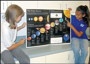 Debbie Snelling, left, points to Pluto, which no longer is classified as a planet.  At right, Azalea Juarez points to Mercury, innermost planet in the solar system. The girls are students in Rhonda Gilbert's fifth-grade class at Kingman Academy of Learning Intermediate School.