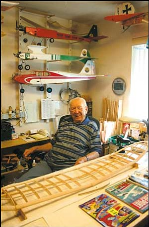 "Robert Baker sits at the desk in his workshop. Part of the ""Zomby"" model airplane he is currently working on can be seen in front of him."