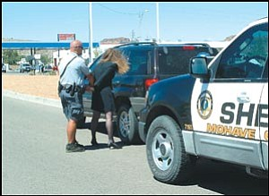 "A Sheriff's deputy ""arrests"" an impaired driver in this staged photo."