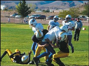 A pair of Kingman Cobras from the Midget division tackle a Lake Havasu player during last week's game at Southside Park. Photo: Courtesy