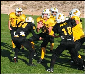 Kingman Pop Warner's Junior Midget Gold team runs into a wall of players from the Black during Saturday's games. The Black Cobras won 28-14. Photo: Courtesy