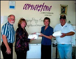 Downey Savings & Loan donated meat from two pigs the company purchased to the Cornerstone Mission at 3049 Sycamore Ave. From left: Gerald Olson, Judy Amber, Melissa Esquerra and Harry Wilson stand in front of the meat cooler holding freshly packaged pork. Photo: NICHOLAS WILBUR/Miner