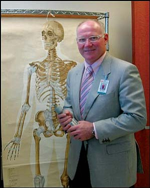 Dr. Emmett McEleney holds a cast saw in front of a 1950s-era picture of the human skeleton. The orthopedic surgeon recently began work at Kingman Regional Medical Center. Photo: TERRY ORGAN/Miner