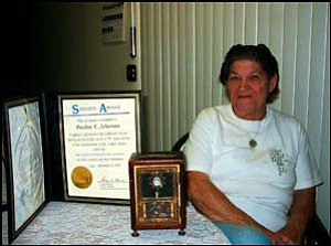 Pauline Schuman shows the certificate she received upon retirement in 1994 from the United States Postal Service, along with a coin bank that looks like a post office box she got in 1986 for having a year's worth of unused sick leave. She now works part time at the Golden Valley Post Office until it closes at the end of January. Photo: TERRY ORGAN/Miner
