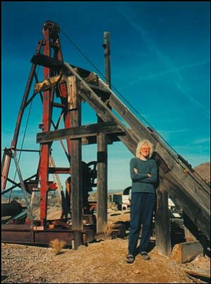 Leslie Kay stands in front of the head frame of the Tuckahoe Mine in Chloride. She and her husband Eldon inherited the mine from his father and owned it until selling it five years ago and moving their family into Kingman. Photo: Courtesy