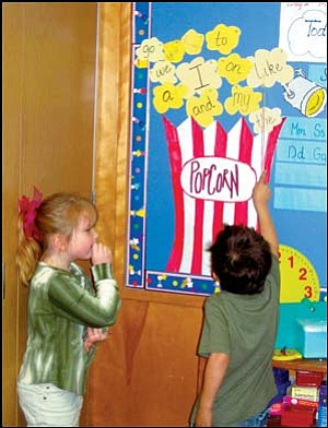 "Madie Miller, left, watches as Gavin Randall points out the word ""like"" Monday in the all-day kindergarten class of Janelle Victory at Manzanita Elementary School. It was part of a ""sight"" exercise in which children recognize and pronounce words they have learned earlier in the school year. Photo: TERRY ORGAN/Miner"