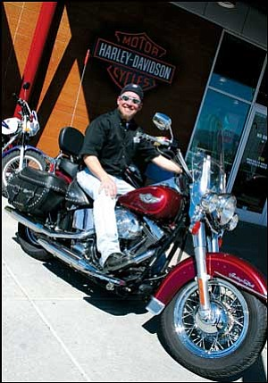Russ Faltersack, sales rep at Mother Road Harley-Davidson, sits atop a Heritage Softtail last Thursday. Classic motorcycles will be one of many items on display April 3 at the store when Harley-Davidson's traveling museum visits Kingman. JC AMBERLYN/Miner