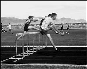 Kingman High's Mike Bartholomew (front) clears a hurdle in the boys 110-meter hurdle race on Wednesday. ROB WEILER/Miner