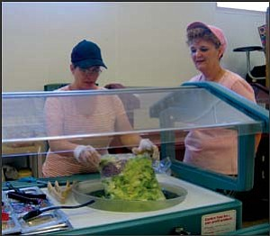 Amy Jyrkinen prepares salad Friday before the first lunch period at Kingman Middle School, where she and Barbara Long, right, are cafeteria workers. TERRY ORGAN/Miner