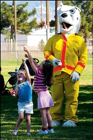Page Booth, 3 (left), and Autumn Wood, 5, try to fly a kite as Sparky the Fire Dog from the Kingman Fire Department watches. The high-flying activity took place at Centennial Park Wednesday afternoon during the 17th Annual Kite Flying Extravaganza. JC AMBERLYN/Miner