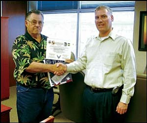 Mohave County Prosecutor Keith J. Evans, right, who just returned from a tour of duty in Iraq, presents an American Flag that was flown on a combat mission in Iraq to Chairman of the Board of Supervisors Pete Byers May 17 at the County Administration Building in Kingman. Courtesy