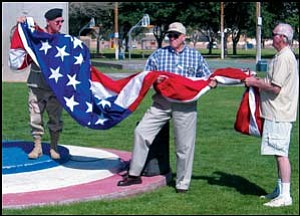 (Left to right) Art Jones, Merle Ward and Don McKenzie hold the American flag during the flag-raising ceremony at Centennial Park Monday. AARON ROYSTER/Miner