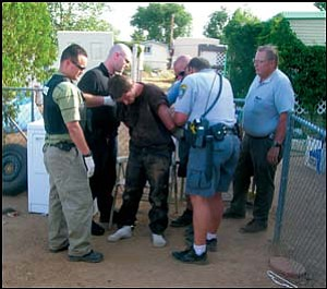 Raymond Coleman, who escaped from the county jail annex June 9, is cuffed after his capture Friday afternoon in North Kingman. Courtesy/MCSO