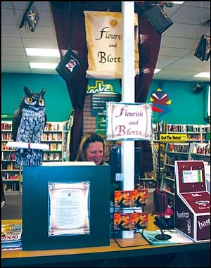 Jan Reed works at a register inside Hastings Tuesday surrounded by Harry Potter-related decorations, some hand-made, like the hanging books, created by employee Carmen Daspit. JC AMBERLYN/Miner