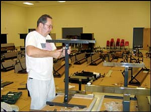 Custodian Bill Bailey assembles a computer table in the multipurpose room of the new Kingman Academy of Learning Primary School on Monday. TERRY ORGAN/Miner