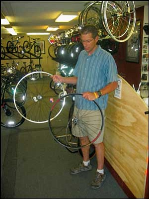 Bicycle Outfitters Owner Ran Hanks holds a single-walled rim in his left hand and a double-walled rim in his right. For off-road riding, Hanks suggests the double rim. AARON ROYSTER/Miner