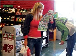 Shoppers were out in force Friday morning after Thanksgiving. Here, Tristin Phillips browses a pamphlet to find out what sales are currently available during her trip to Hastings Entertainment Store.  Rachael Brady is behind her looking at a sales rack. JC AMBERLYN/Miner