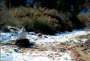A snowman stands along a path at Lazy YU Ranch in the Hualapai foothills after a storm passed through the Kingman area last week. More of the same is expected Wednesday. JC AMBERLYN/Miner