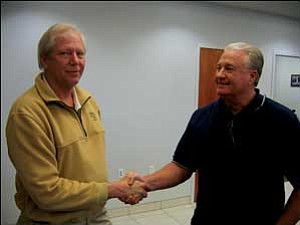 Las Vegas developer Jim Rhodes and local businessman Scott Dunton shake hands inside the new administration building at the Kingman airport Tuesday before signing a settlement to a three-year lawsuit and negotiating terms that both parties believe will be good for them, the city and Mohave County.  NICHOLAS WILBUR/Miner
