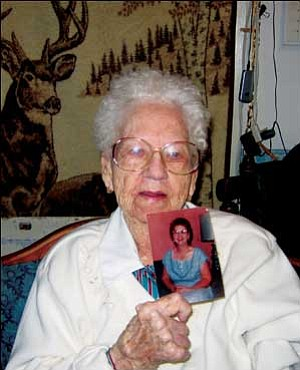 Evie O. Gilbert, who turns 100 on Feb. 29, holds a picture of herself taken in the late 1950s. TERRY ORGAN/Miner