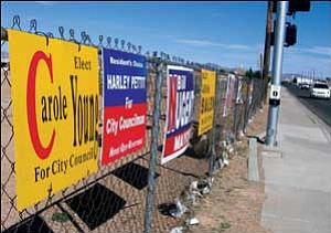 Six candidates have signs posted on the fence across from the Wal-Mart entrance on Airway Avenue. Of the 11 total candidates for mayor and City Council who have purchased signs, mayoral candidate Bill Nugent has spent the most, with $4,870. NICHOLAS WILBUR/ Miner