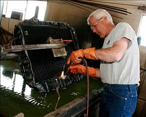 Jim Cave works at his radiator shop Thursday afternoon. His business has been plagued with problems resulting from vagrants attracted to nearby Cornerstone Mission.