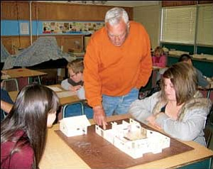 Al Snyder talks with Kyla Richhart, left, and Isabella Goldberg on Monday about their scale-model home. He is instructing 23 students in Gail Arnold's fifth-grade accelerated class at Manzanita Elementary School in the project. TERRY ORGAN/Miner