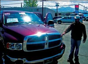 Dave Watson, a salesman at 66 Auto Sales, shows a 2002 Dodge Ram to a browsing customer Thursday morning. The company has been in business 33 years, specializing in low-mileage pre-owned vehicles. NICHOLAS WILBUR/Miner