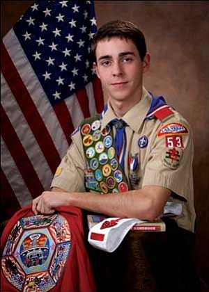 Cody Palm, who obtained Eagle Scout, poses in his Boys Scouts of American uniform adorned with badges and awards.  Courtesy