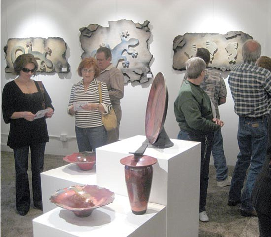 SUZANNE ADAMS/ Miner<br><br> Local residents crowded around one of many different works of art in Kingman's newest art gallery inside the Beale Street Brews coffee shop Friday evening.