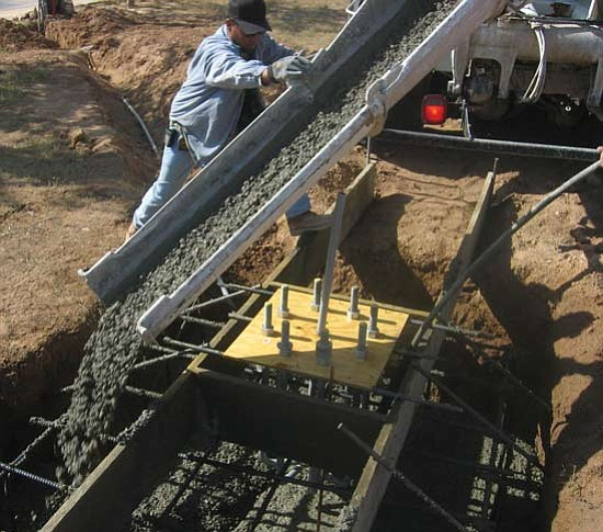 JAMES CHILTON/Miner<br><br> Efren Lamas of Pure Steel Concrete directs fresh concrete into the foundation hole dug for Dr. John Lingenfelter's wind turbine at 1080 Riata Valley Road.