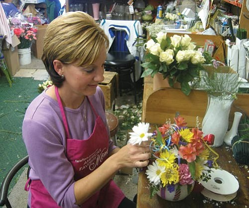 JAMES CHILTON/Miner<br><br> Kathleen Scott, the new owner of the Mandarin Orchid House, arranges flowers in a back room Friday morning