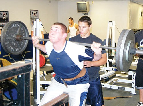 SHAWN BYRNE/Miner<br><br> Trey Gilleo, a graduating senior at Kingman High, squats 245 pounds Tuesday during a workout. Gilleo will be playing for the Northern Arizona Lumberjacks next season. Returning tailback Jonathan Oakie spots for Gilleo.