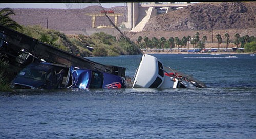 Courtesy<br><br> A section of fence clings to the tractor-trailer that plummeted off the Laughlin side of the Colorado River Wednesday afternoon closing the bridge between Bullhead City and Laughlin for several hours.
