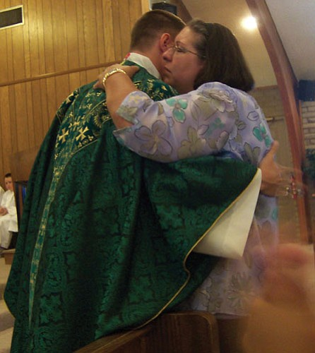 Courtesy<br><br> The Rev. Arthur L. Nave Jr. hugs his mother, Mary, during his first Mass at St. Mary's Catholic Church in Kingman on Sunday.
