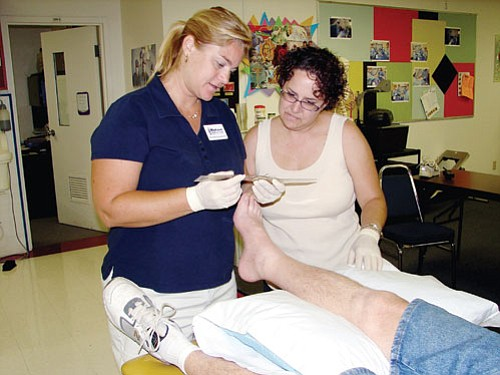 MCC/Courtesy<br><br> Cheryl Pike, right, looks on as Rhonda Schnabl, left, the director of the physical therapist assistant program at Mohave Community College, takes a measurement of a patient's foot while checking out the equipment on hand for the program to begin this fall at MCC.