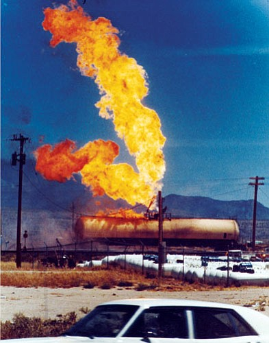 MOHAVE MUSEUM/Courtesy<br> Onlookers drive by while fire streams from a vent and an impingement of a Doxol Propane railroad tanker car on July 5, 1973, in Kingman.